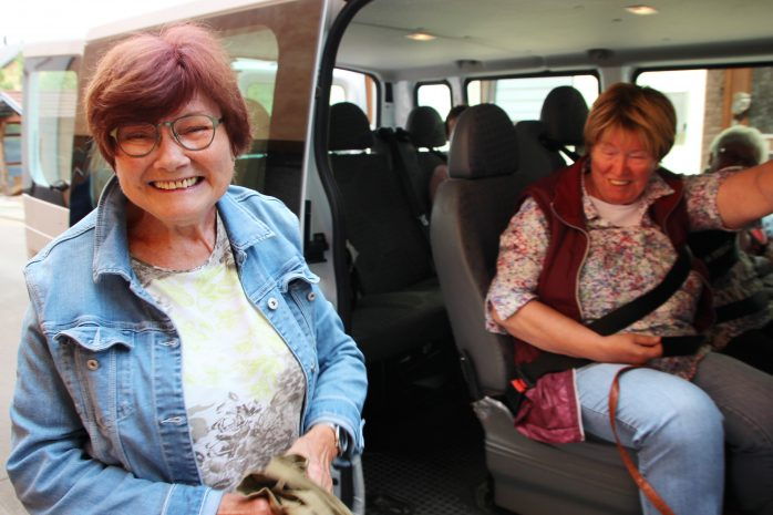 Frau steigt lächelnd aus dem Bürgerbus